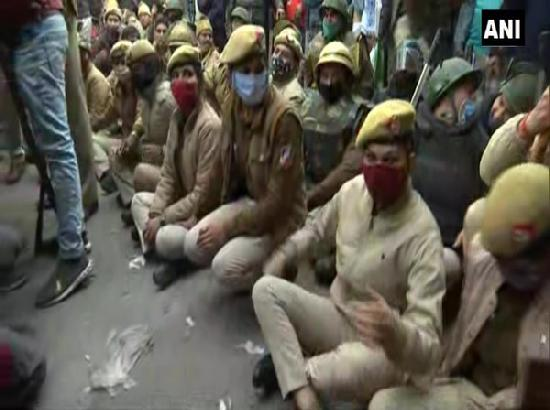 Police personnel sit on road in Nangloi to block farmers' tractor rally